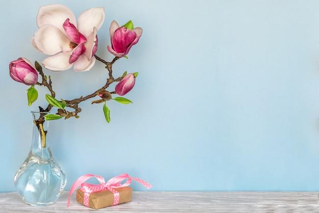 Stillleben mit schönen frühlingsmagnolienblumen und -geschenkbox. muttertag hintergrund