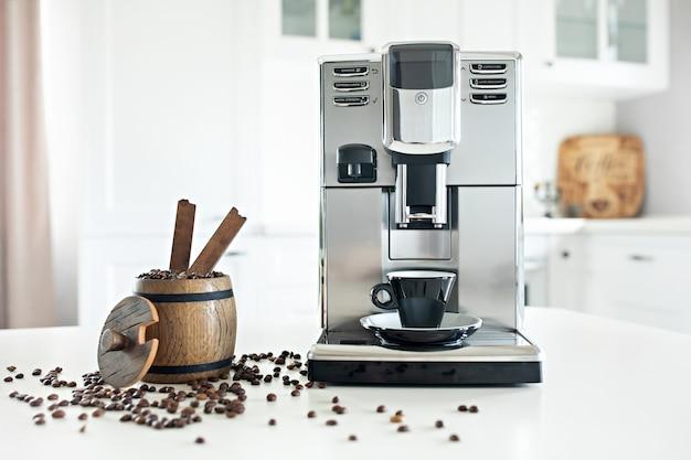 Stillleben mit selbst gemachter kaffeemaschine auf dem küchentisch mit hölzernem behälter mit kaffeebohnen.