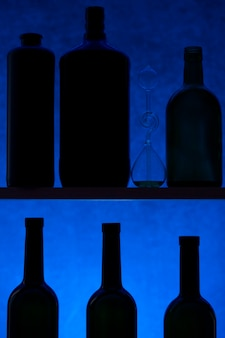 Stillleben mit silhouetten von flaschen auf einer blauen oberfläche
