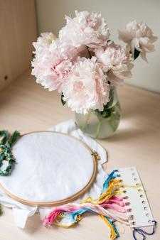 Stillleben mit stickset für kreuzstiche und vase mit pfingstrosen weißer stoffstickerei