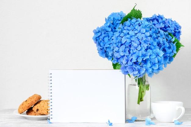 Stillleben mit strauß blauer hortensienblüten, leerer grußkarte, tasse kaffee und kekse.