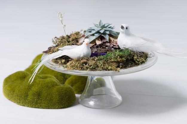 Stillleben mit tafelaufsatz mit zwei weißen tauben, moos und flechten auf sockel-kuchenständer