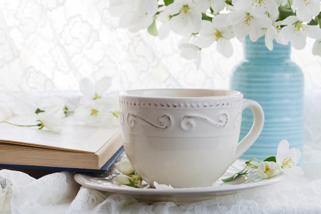 Stillleben mit teetasse und blütenzweig