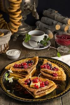 Stillleben mit traditionellen ukrainischen und russischen pfannkuchen für den maslenitsa-urlaub mit butter und beeren auf einem schwarzen tablett mit samowar