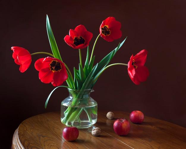 Stillleben mit tulpenbouquet, äpfeln und nüssen.