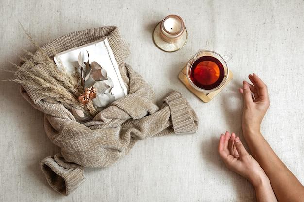 Stillleben mit weiblichen händen, einer tasse tee und getrockneten blumen auf einem warmen pullover, das konzept der herbstkomfort-draufsicht.