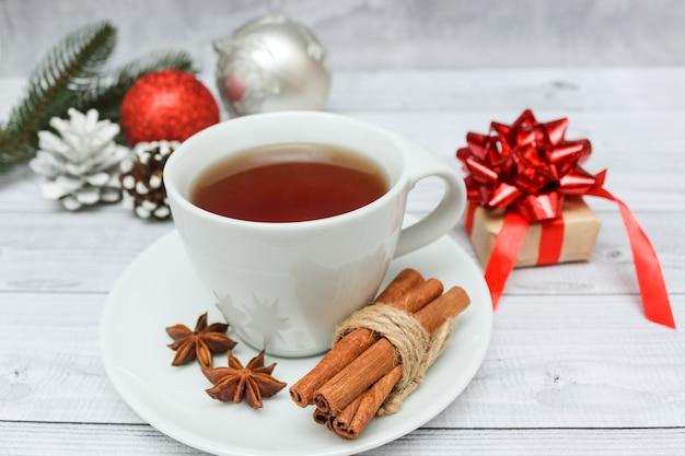 Stillleben mit weihnachtsschmuck, einer tasse tee mit gewürzen und einem grob gestrickten wollpullover.