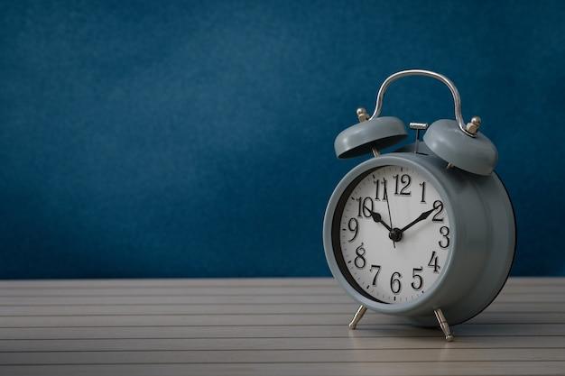 Stillleben mit weinlesewecker zeigt 10.10 uhr auf rustikalem blauem hintergrund