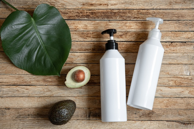 Stillleben mit weißen modellflaschen mit spender und avocado. bio-kosmetik und beauty-konzept.