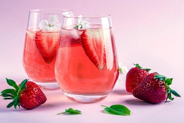 Stillleben mit zwei gläsern kühlenden erdbeer-sangria mit sekt, erdbeere, eiswürfeln