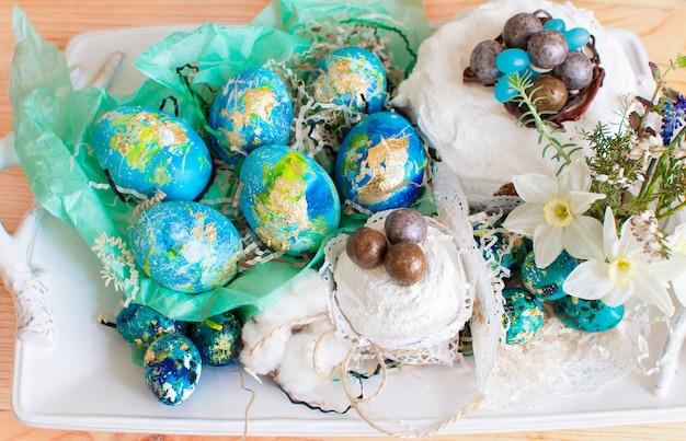 Stillleben ostern hühnereier und wachteleier in einem nest, kuchen mit schokolade und narzissen dekoriert. osterferienkonzept