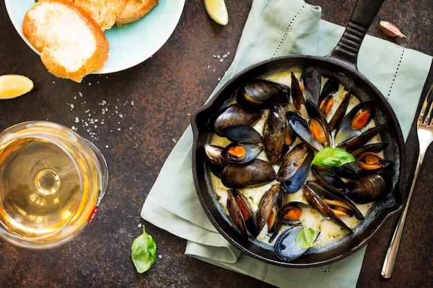 Stillleben restaurant abendessen gekochte muscheln in weißweinsauce mit einem glas weißwein weißbrot toast und zitronenscheiben flache lage draufsicht