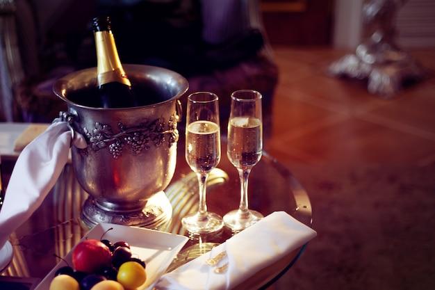 Stillleben, romantisches abendessen, zwei gläser und champagner im eiskübel. feier oder feiertag