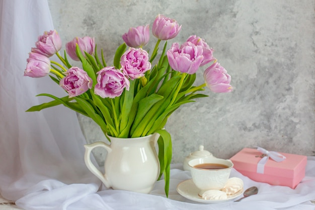 Stillleben-strauß tulpen in einem vase-teetassengeschenk