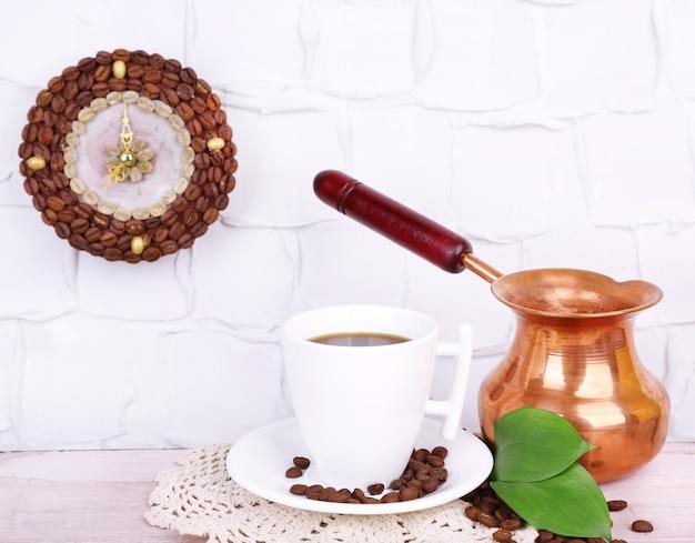 Stillleben tasse kaffee und uhr, an grauer wand