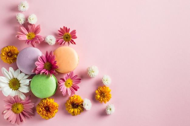 Stillleben- und lebensmittelfoto von kuchen macarons in einer geschenkbox mit blumen, eine tasse tee auf hellem hintergrund. bonbon- und nachtischkonzept von makronen.