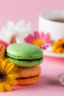 Stillleben und lebensmittelfoto von kuchenmakarons in einer geschenkbox mit blumen, eine tasse tee auf licht