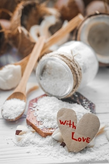 Stillleben valentinstag mit kokosnuss und herz, holzlöffel mit kokosnuss auf holzhintergrund