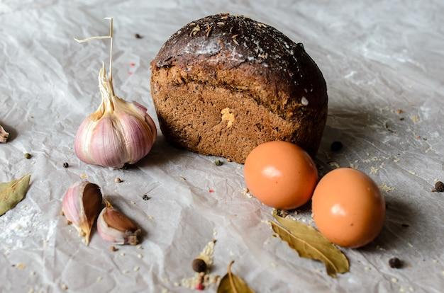 Stillleben von brot, eiern, knoblauch und gewürzen.