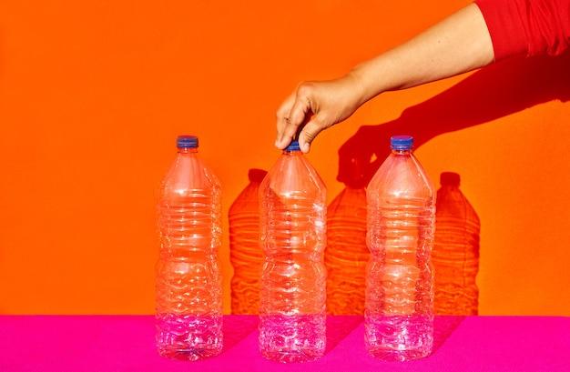 Stillleben von drei plastikflaschen mit einer hand, die eine davon hält. recycling, umweltkonzept