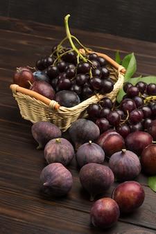 Stillleben von früchten. weintraube im weidenkorb. feigen und pflaumen auf dem tisch. dunkler hölzerner hintergrund. draufsicht