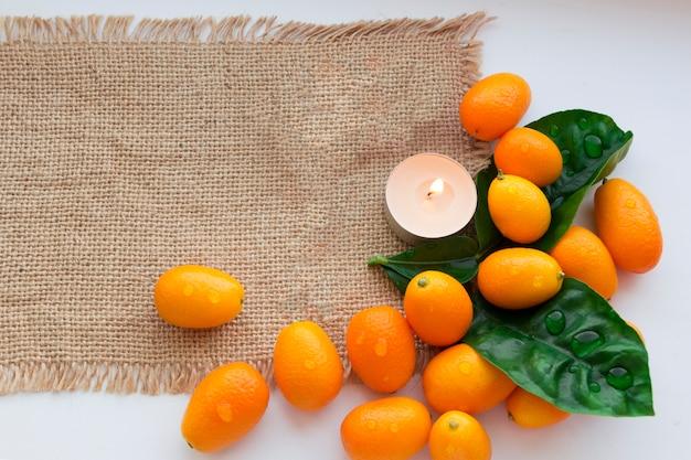 Stillleben von japanischen orangen und kerzen auf sackleinen. entspannender hintergrund. hintergrund für spa-design.