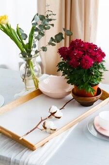 Stillleben von rosa tellern und tassen auf einem tisch mit blumen