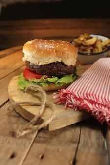 Stillleben von rustikalem burger, kartoffeln und requisiten