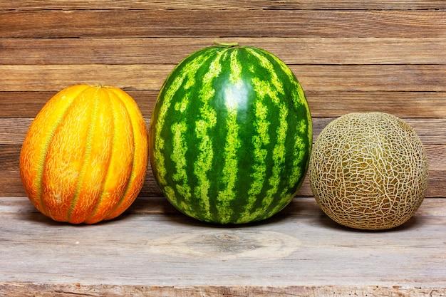 Stillleben von verschiedenen arten der melone, wassermelone auf altem hölzernem retro-