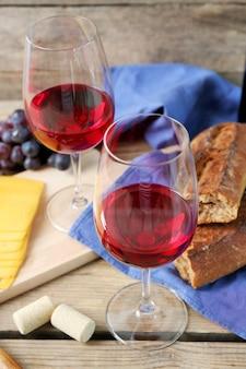 Stillleben von wein, trauben, käse und brot auf rustikalem holz