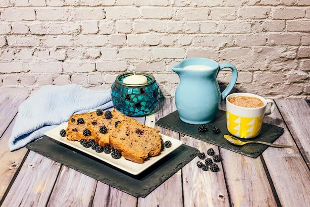 Stillleben von wildobstkuchen mit tasse milch mit kakao und milchkännchen.