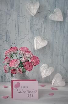 Stillleben zum valentinstag mit leerer papierkarte, rosa rosen und girlandenlichtern in form von papierherzen auf rustikalem hintergrund