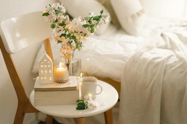 Stilllebendetails im hauptinnenraum des wohnzimmers. buch, heiße tasse tee, kerze und vase mit apfelfrühlingsblumen. lesen und ausruhen