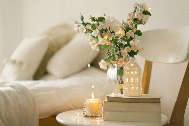 Stilllebendetails im hauptinnenraum des wohnzimmers. buch, kerze und vase mit apfelfrühlingsblumen. lesen und ausruhen