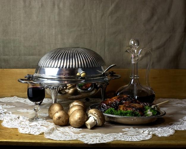 Stilllebenfoto von karaffe und glas portwein, antikem chafing dish, pilzen und brathähnchen