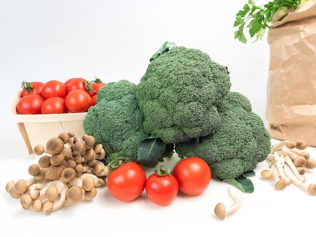 Stilllebengemüsekohlbrokkoli mit tomatenpilzgrün lässt weißes isolat