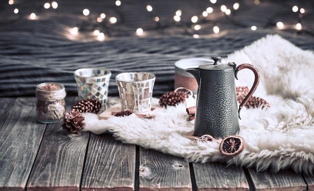 Stilllebenhausdekorationen mit einer teekanne auf einem hölzernen hintergrund im innenraum des raumes mit licht im hintergrund, ein feiertagskonzept