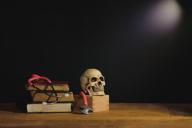 Stilllebenmalereiphotographie mit dem menschlichen schädel auf lehrbuch.