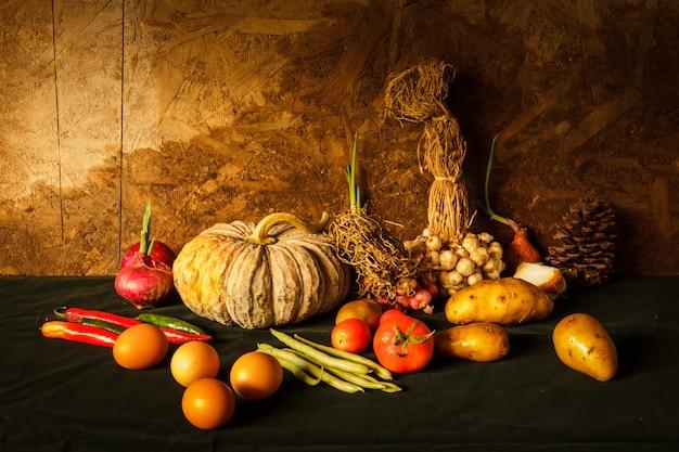 Stilllebenphotographie mit kürbis, gewürzen, kräutern, gemüse und früchten.