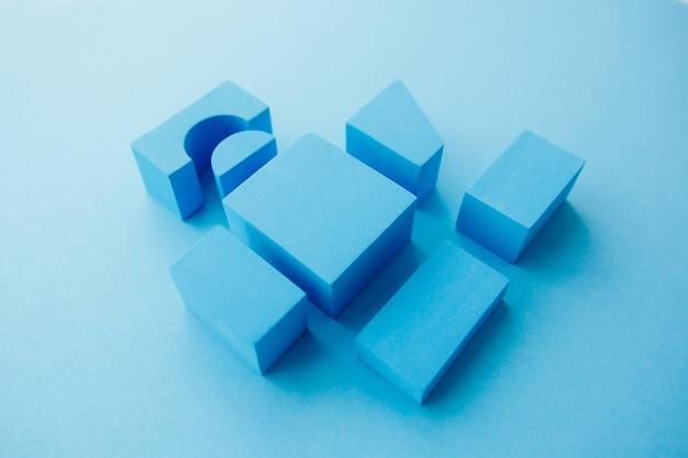 Stilllebenzusammensetzung der geometrischen zahlen. würfel und andere gegenstände auf blauem hintergrund.