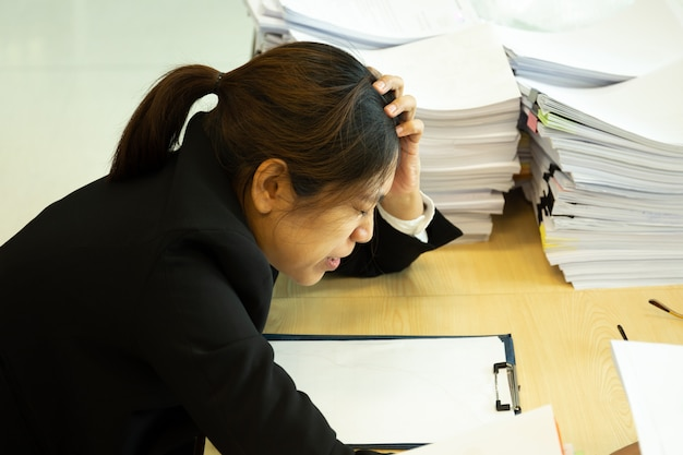 Stillstehende hände der geschäftsfrau auf kopf mit augen schließen am arbeitsschreibtisch im büro.