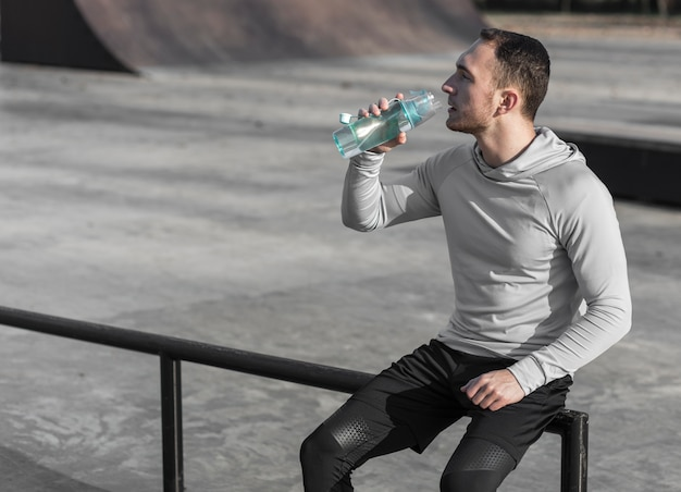 Stillstehendes und trinkwasser des jungen mannes