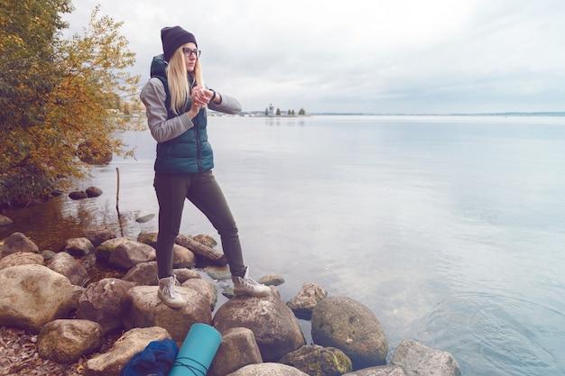 Stilvoll gekleidete blonde sportlerin stellt einen elektronischen armband-schrittzähler ein
