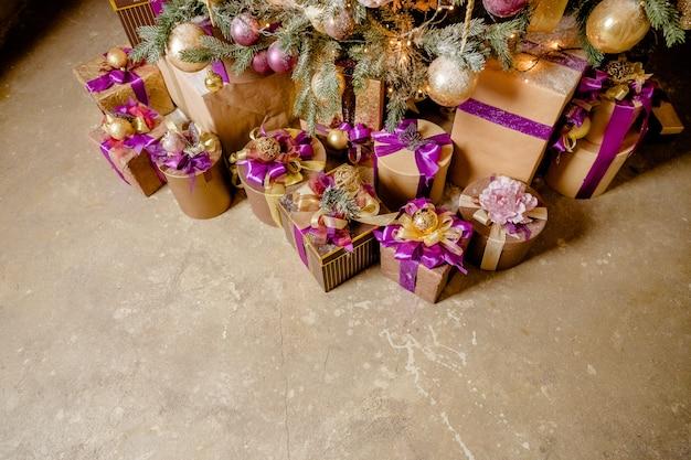 Stilvoll gewickelt lila und golden und geschenkboxen unter dem weihnachtsbaum
