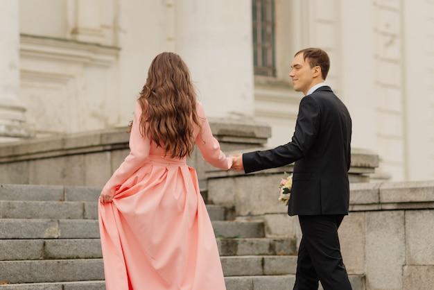 Stilvoll nur verheiratet. hochzeitspaar. schließen sie. glückliches brautpaar, das nahe altem schloss geht. brauthochzeitsstrauß der blume