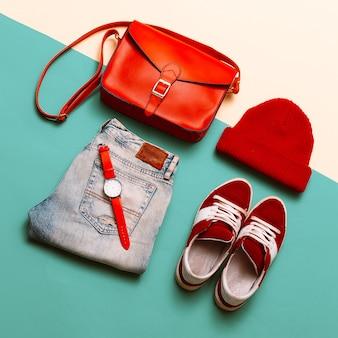 Stilvolle accessoires und kleidung. konzentriere dich auf rot. handtaschen, mützen, uhren. turnschuhe. urban style, denim