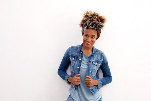 Stilvolle afrikanische frau, die gegen weißen hintergrund lächelt