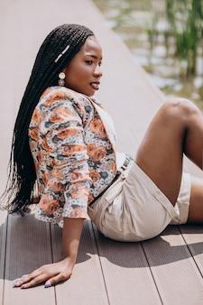 Stilvolle afroamerikanerfrau, die durch den see im park sitzt