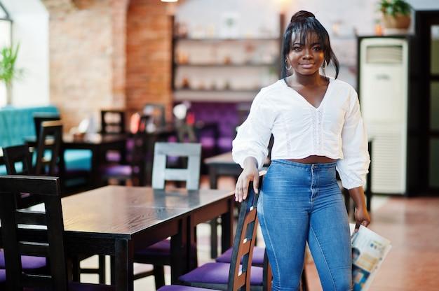 Stilvolle afroamerikanerfrauen in der weißen bluse und in den blauen jeans stellten im café mit zeitung auf.