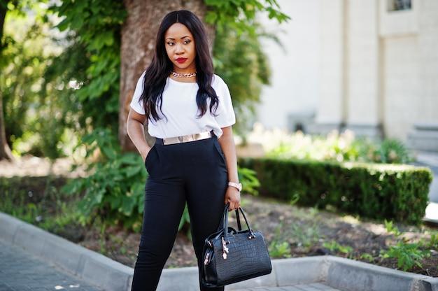 Stilvolle afroamerikanergeschäftsfrau auf straßen der stadt.
